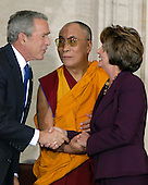 Washington, DC - October 17, 2007 -- United States President George W. Bush, left, The 14th Dalai Lama, Tenzin Gyatso, center, and Speaker of the House Nancy Pelosi (Democrat of California), right, share a three-way handshake during a ceremony where the Dalai Lama accepts the Congressional Gold Medal, the nation's highest and most distinguished civilian award, in Washington, D.C. on Wednesday, October 17, 2007..Credit: Ron Sachs/CNP