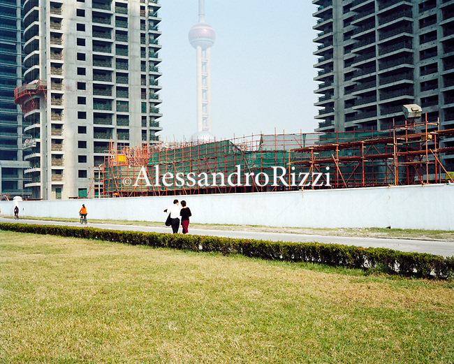 A couple walking in Pudong area near some building under costruction