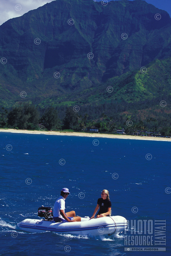 Couple riding inflatable boat in off white sand beach, Mount Waialeale in background, Hanalei Bay, Kauai, Hawaii