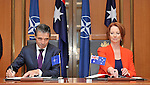 Secretary General of NATO Anders Rasmussen L and Australian Prime Minister Julia Gillard R exchange sign a joint decleration between Australia and NATO  at Parliament House Canberra, on Thursday June 14th 2012. AFP PHOTO / Mark GRAHAM