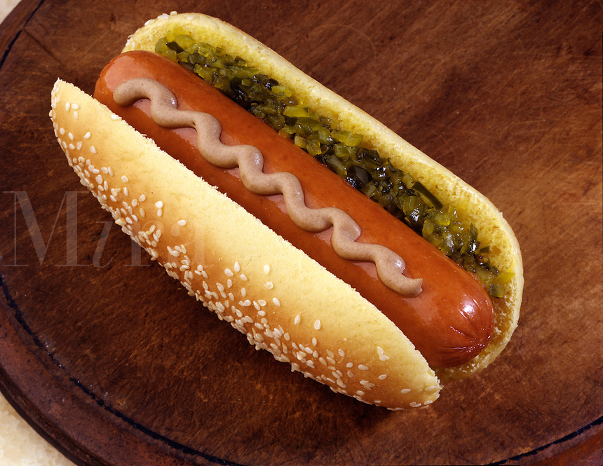 A hot dog on a seeded bun with mustard and relish