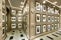 A collection of black and white photographs is displayed in  rows in a hallway lit by wall lamps.