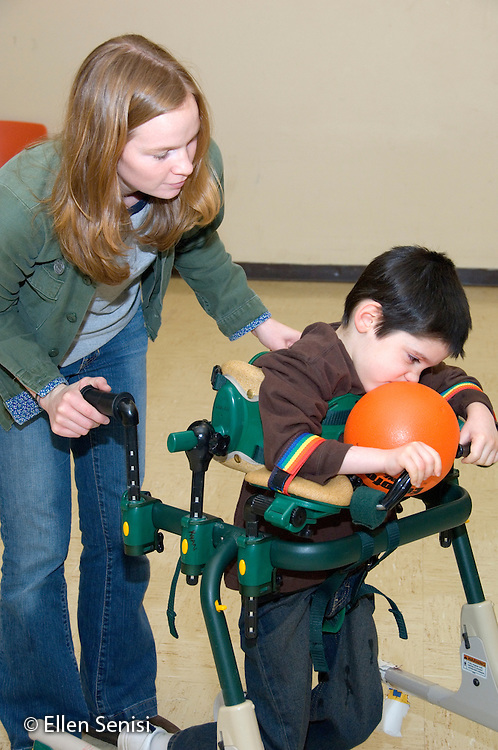 MR / Albany, NY.Langan School at Center for Disability Services .Ungraded private school which serves individuals with multiple disabilities.Teaching assistant moves child in a gait trainer as he grasps the ball to try to tag someone out during a modified Adaptive Physical Education class (APE) game of T-ball.  Boy: 8, cerebral palsy, spastic quadriplegic, nonverbal with expressive and receptive language delays.MR: Neu1; Hac2.© Ellen B. Senisi