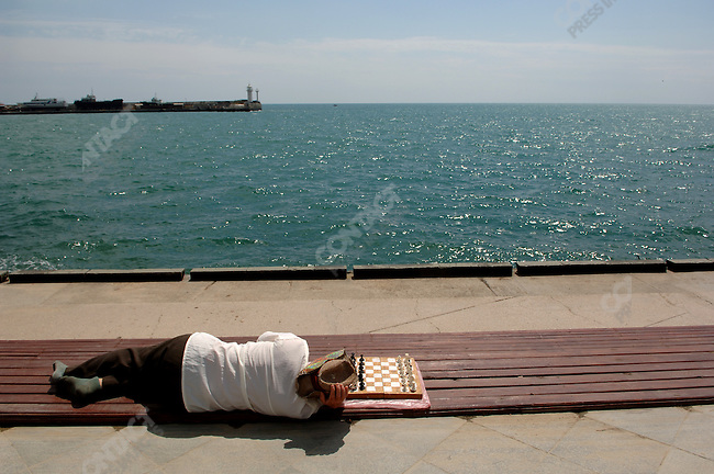 A man waits for a chess game on the searfront promenade in Yalta. Republic of Crimea, May 27, 2006.