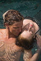 Young couple floating in water, elevated view