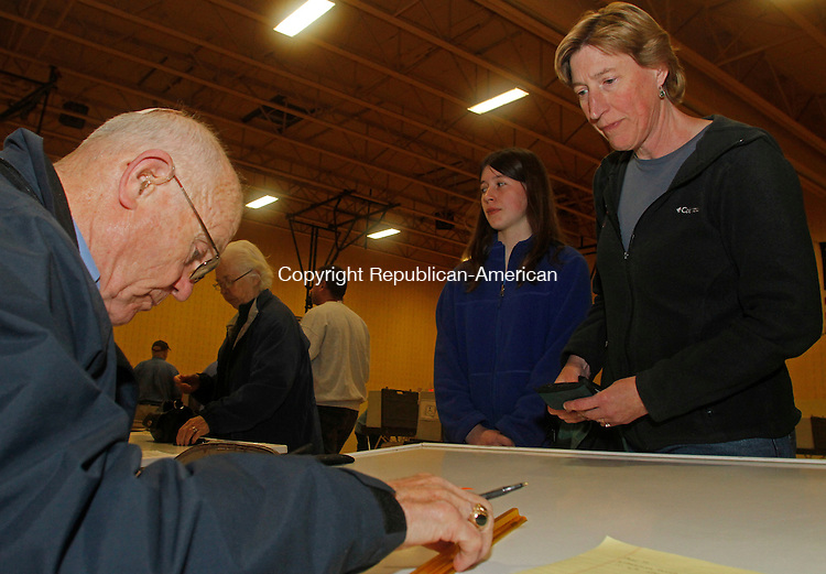 Winsted, CT-110414MK01 Poll worker Neil Kelsey checks Marie Cavanaugh in to vote as her daughter Sarah looks on at Pearson Middle School in Winsted Tuesday evening.  Michael Kabelka / Republican-American.