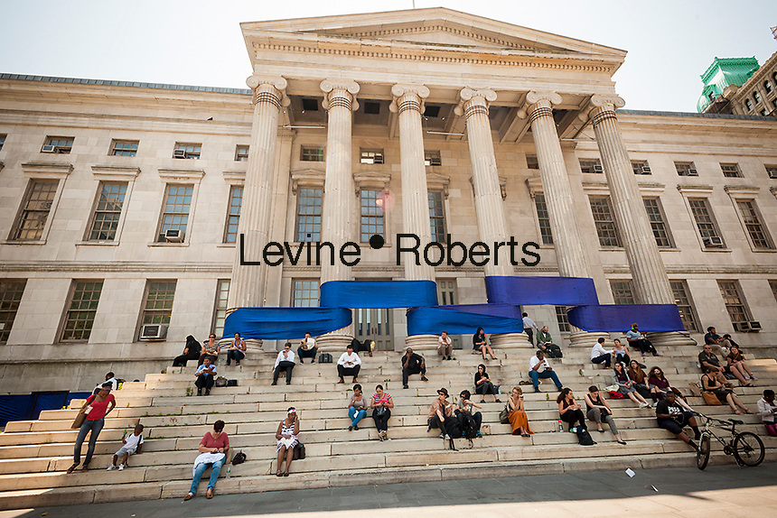 Office workers on their lunch hour sit on the steps of Brooklyn Borough Hall in the New York borough of Brooklyn on Friday, June 24, 2016 in front of the blue part of a rainbow ribbon wrapped around the building in honor of Gay Pride. (© Richard B. Levine)