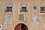 Windows with red flowers, and iron grill, and two fresco below, in the small town of Viscoprano, a Swiss town in the Bregaglia Valley which dates back to 1096