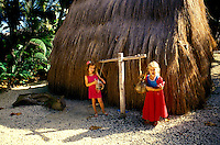 "Two young girls in red clothes play outside of a """"grass hut""""."