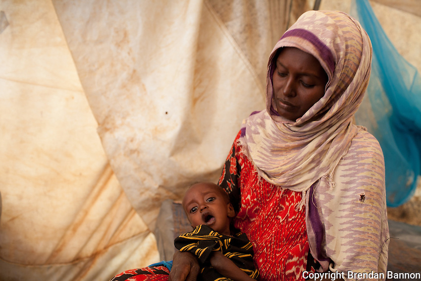 """Fatuma Badel fled Buale, Somalia with 8 children after leaving her sick husband. """"he became sick and I couldn't carry him. I don't know if he is alive or dead. This one, my youngest was like a dead person when i arrived. Now I thank God I can hear him cry again."""" She has been  3 days in the MSF hospital with her baby Mohamud who arribvedseverely malnourished. At nine months old he weighs 4.3 KG. Dadaab refugee camp, kenya July 22, 2011. Photo: Brendan Bannon"""