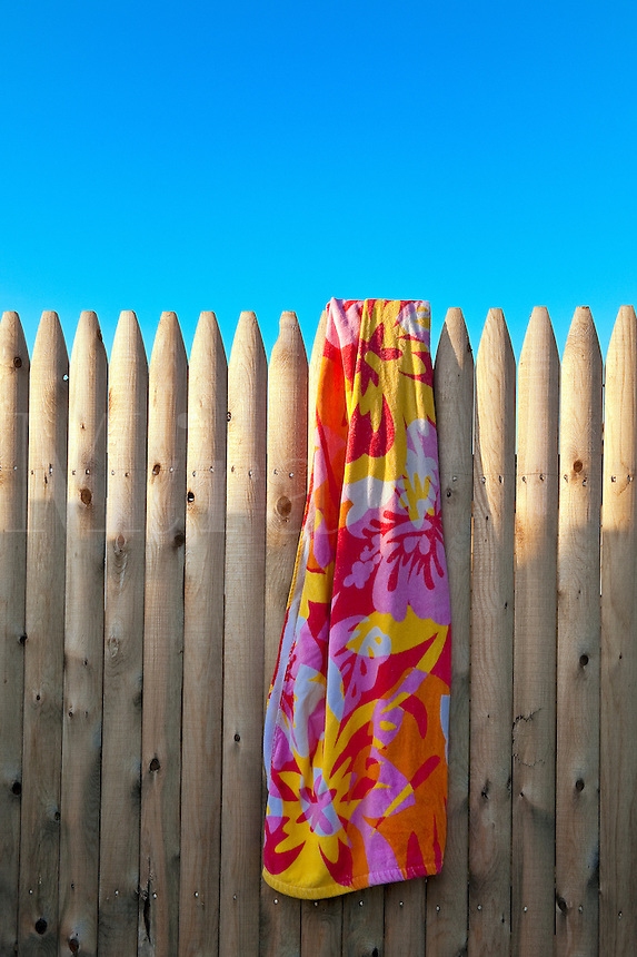 Beach towel hanging on a fence.