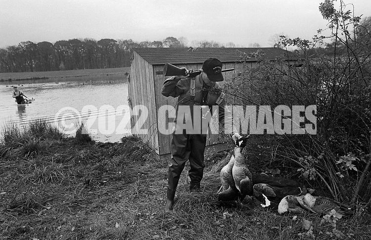 Bill Lewis places a goose onto a pile of dead geese that they had shot as Ron Kobli fetches the decoys from the pond Saturday November 2, 1991 in Buckingham, Pennsylvania. (Photo by William Thomas Cain)