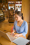 27 year old Korean female student with cross around her neck works on computer laptop at table in coffee shop alone