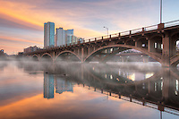 Fog comes off the water of Lady Bird Lake at Lamar Bridge on a cold January morning. In the distance are a few high rises of the Austin skyline.