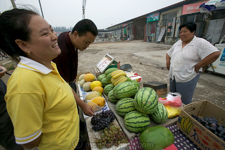 Li Jinxian always likes to buy fruit from the same vendor, a woman whom she has built a rapport with over time. This week her husband, Cui Haiwang, has come shopping with her; usually he's away working in Beijing. Both husband and wife are discriminating fruit and vegetable shoppers. Sniffing and pinching each item before deciding on a purchase is standard operating procedure. Hungry Planet: What the World Eats (p. 85). The Cui family of Weitaiwu village, Beijing Province, China, is one of the thirty families featured, with a weeks' worth of food, in the book Hungry Planet: What the World Eats.