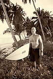 INDONESIA, Mentawai Islands, Kandui Surf Resort, portrait of mature man standing with surfboard (B&W)