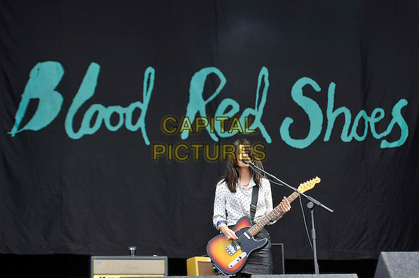 Laura-Mary Carter of Blood Red Shoes.performing live on stage at Reading Festival, Reading, England, UK, .25th August 2012..music concert gig half length playing guitar white blue polka dot shirt black leather skirt microphone singing .CAP/MAR.© Martin Harris/Capital Pictures.
