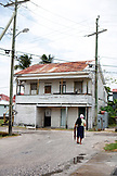 BELIZE. Belize City, an elderly woman walks down the street in front of the Museum of Belize