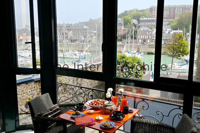 A small breakfast area in an enclosed balcony overlooks the harbour