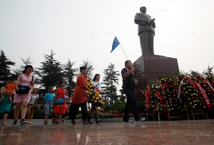 Visitors offer a flower reef to a statue of Mao Zedong at the Statue Square near Mao's birthplace in Shaoshan, Hunan Province, China on 12 August 2009.