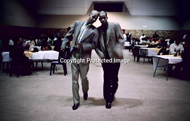 SOWETO, SOUTH AFRICA APRIL 23: Unidentified twin brothers perform a dance during a late night session at a Jazz club on April 23, 2005 in Diepkloof Hall in Soweto, Johannesburg, South Africa. The club has monthly sessions where people come to enjoy classic jazz music, eat and have a few drinks. People are encouraged to perform dance numbers to their favorite tunes. Soweto is South Africa?s largest township and it was founded about one hundred years to make housing available for black people south west of downtown Johannesburg. The estimated population is between 2-3 million. Many key events during the Apartheid struggle unfolded here, and the most known is the student uprisings in June 1976, where thousands of students took to the streets to protest after being forced to study the Afrikaans language at school. Soweto today is a mix of old housing and newly constructed townhouses. A new hungry black middle-class is growing steadily. Most residents work in Johannesburg but the last years many shopping malls has been built, and people are starting to spend their money in Soweto.(Photo by Per-Anders Pettersson)