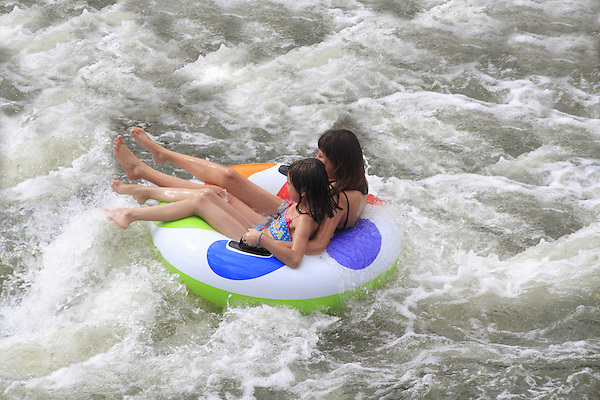 Girls floating in inner tube at Boulder Creek, Boulder, Colorado. .  John offers private photo tours in Denver, Boulder and throughout Colorado. Year-round.