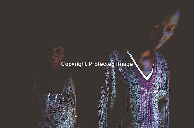 SIAIDSG20348.Social Issues. AIDS. People Children. Kwazulu Natal. Young man with AIDS standing next to his mother. The darkness of this image depicts the nature of the deathly virus. .©Per-Anders Pettersson / iAfrika Photos