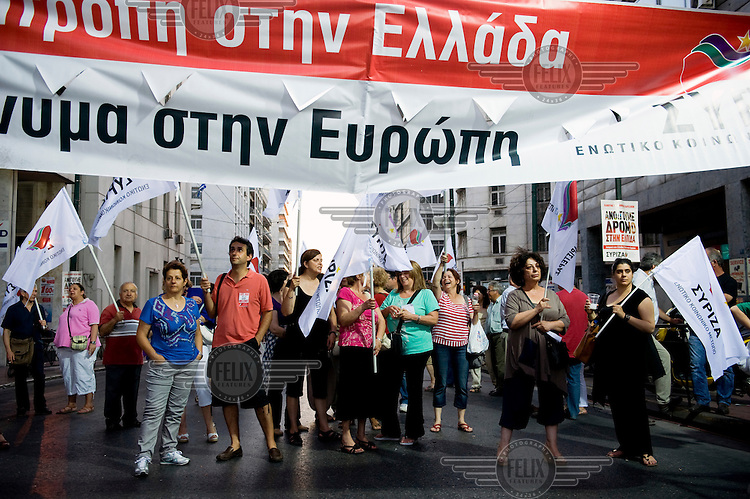 People holding banners and flags stand on a street during a Syriza coalition campaign rally before the 17 June 2012 Greek re-run election on Omonia Square in Athens. The election saw New Democracy, the centre right party, win a small majority of the votes. .