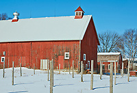 A red barn sits waiting for the snow to melt and the farm to become active again. Door County, Wisconsin