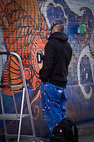 A graffiti artist uses an aerosol paint can to create a piece in Toronto April 23, 2010.
