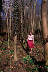 A912MA Young girl in red skirt and pink top in daffodil woods in English spring.
