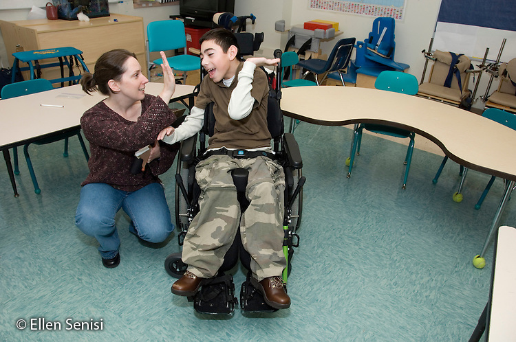 "MR / Albany, NY.Langan School at Center for Disability Services (private nonprofit disability services).Upper elementary classroom/Day Program.Speech language pathologist and child give each other a ""high five"" (slap hands). Boy: 11, cerebral palsy, expressive and receptive language delays.MR: Bro12; Dub1.© Ellen B. Senisi"