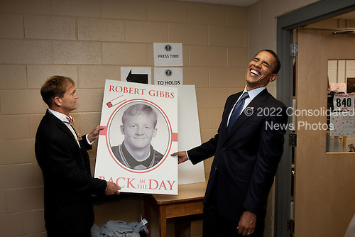 Raleigh, NC - July 29, 2009 -- United States President Barack Obama laughs at a picture of a younger Press Secretary Robert Gibbs following a town hall meeting at Broughton High School in Raleigh, North Carolina on July 29, 2009.  .Mandatory Credit: Pete Souza - White House via CNP