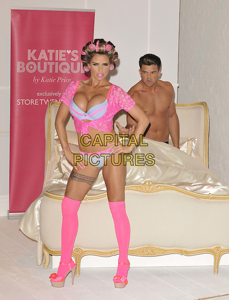 Katie Price (Jordan) & Leandro Penna.The launch photocall for Katie Price's new summer lingerie range for Store 21, The Worx, London, England..May 29th, 2012.full length pink lace top knotted bra cleavage belly stomach midriff knickers underwear tights stockings tattoo garter beige platform sandals shoes rollers curlers in hair side bed chest topless couple hands on hips fist hand arm funny .CAP/CAN.©Can Nguyen/Capital Pictures.