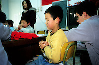 CHINA. Beijing. A young orphan prays in an orphanage outside of Beijing being visited by a local Christian group. 2007. There are currently millions of orphans in China living in orphanages spread throughout the country. As a result of China's one-child policy, many children are abandoned or given up if they suffer from any physical or mental handicap as the parents strive to have a child born 'normal' and well. This has led to may children being abandoned to live in state and privately-owned orphanages.