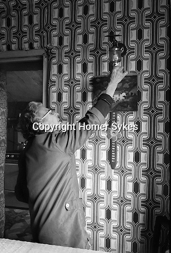 Cornwall, woman lighting gas lamp in her cottage 1978.