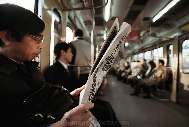 Kazuo Ukita reads his newspaper on the train taking him from Kodaira City to his workplace where he fills orders in a book and magazine warehouse. Japan. Material World Project. The Ukita family lives in a 1421 square foot wooden frame house in a suburb northwest of Tokyo called Kodaira City.