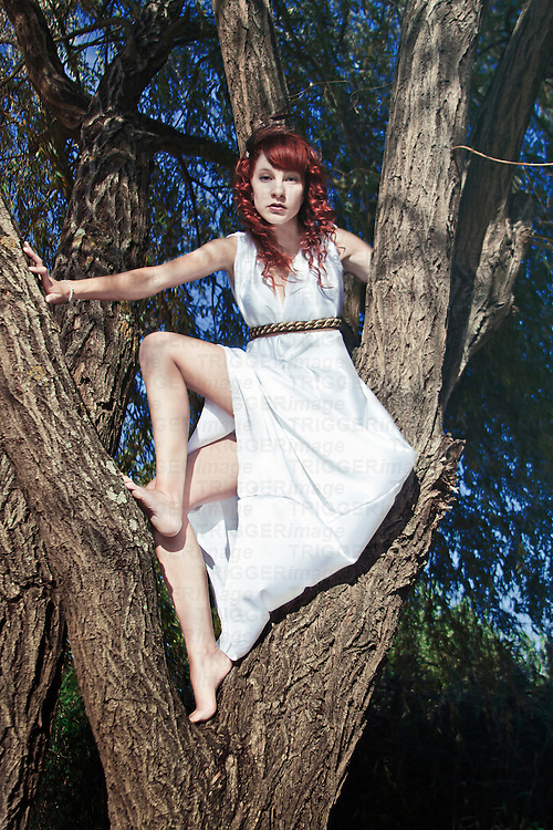 Full body portrait of a young woman/nymph with a long white dress and red curly hair, posing against a tree in a natural place.