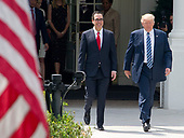 United States President Donald J. Trump walks to the US Treasury Building with US Secretary of the Treasury Steven Mnuchin to sign Executive Orders concerning financial services in Washington, DC on April 21, 2017.<br /> Credit: Ron Sachs / Pool via CNP