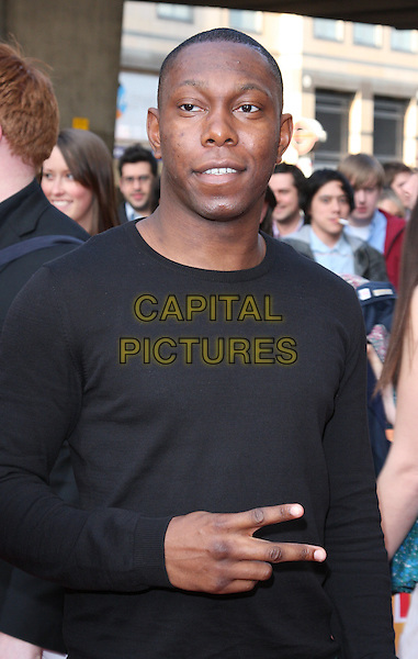 DIZZEE RASCAL (Dylan Kwabena Mills).Attending the World Premiere of  'The Infidel' at the Hammersmith Apollo, London, England, UK, April 8th 2010.arrivals half length hand v peace sign gesture black top jumper sweater .CAP/ROS.©Steve Ross/Capital Pictures.
