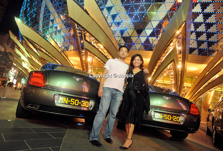 "A pair of gamblers (husband and wife) pose outside the Lisboa Casino, Macau, 25th October 2008.  Macau is known simply as ""Vegas"" in China. The former Potuguese colony, now a Chinese Special Administrative Region, attracts millions of Chinese gamblers annually and last year earned more gambling dollars than Las Vegas."