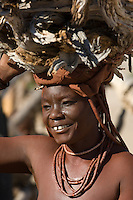 The Himba are a minority group in Namibia, representing less than one per cent of the population. They dust their skin with an ochre dye and never wash. The women go bare-breasted and cover their lower bodies with cloths and animal skins. This woman is carrying firewood back to the stockade.