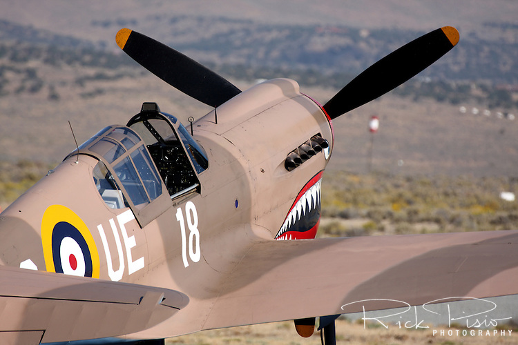"""A Curtiss P-40 Warhawk sits on the ramp during the Reno National Championship Air Races. The Curtiss Aircraft Co.'s P-40 Warhawk fighter was the last of the """"Hawk"""" line of aircraft produced in the 1930's & 40's. An early prototype version of the P-40 was the first American fighter capable of speeds greater than 300 MPH. Utilized in most theatres of the Second World War the aircraft was used to great effectiveness by Claire Chenault's American Volunteer Group, the Flying Tigers, who painted menacing shark mouths on their aircraft. Even with the success of the Flying Tigers in China against the Japanese the P-40's performance was quickly eclipsed by the newer aircraft of the time."""