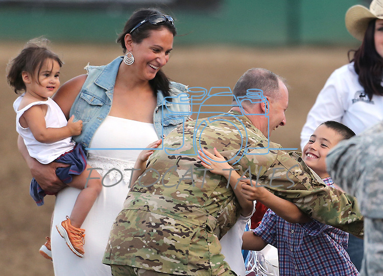 Nevada Army National Guard Chief Warrant Officer Glen Spadin gets hugs from his wife Maja, left, their dauther Rebecca, 2, and son Mark, 9, after his surprise return from Afghanistan during Patriot Night at the Reno Rodeo in Reno, Nev. on Friday, June 19, 2015. Spadin returned after a year in Afghanistan to surprise his six children. <br /> Photo by Cathleen Allison