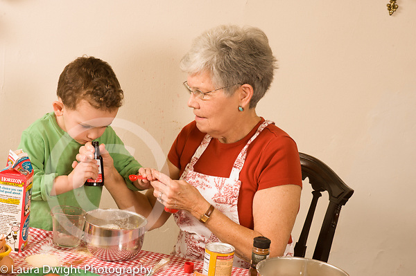 3 year old boy cooking baking activity with grandmother smelling vanilla extract in bottle she holds
