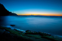 The setting sun streaking gold across the horizon as the blue hour colors the rocks at Ke'e Beach and the cliffs of Na Pali, Kauai.