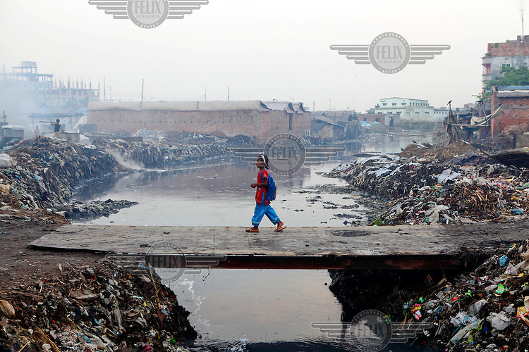 A girl crosses a bridge over the heavily polluted Buriganga River. Everyday 1.5 million cubic metres of waste water from 7,000 industrial units in surrounding areas and another 0.5 million cubic metres from other sources are released into the river. Although the government have enacted laws that require industry to safely process effluents these are rarely enforced and pollution remains uncontrolled. The river is biologically dead and increasingly a serious health hazard to those using and living near it.