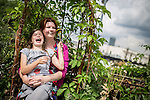 © Joel Goodman - 07973 332324 . 27 July 2013 . Hulme Community Garden Centre , Old Birley Street , Hulme , Manchester M15 , UK . Mum Kerrie Wilson with daughter Amy Wilson (eight) (both correct) (from Rusholme) sit in the roof garden . Hulme is Where the Art Is festival . Photo credit : Joel Goodman