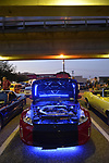 Bellmore, NY, USA. August 24, 2018. Red 2014 Nissan 370Z, with open hood showing engine area lit blue, is parked under elevated tracks that  LIRR train is traveling on, during Bellmore Friday Night Car Show.