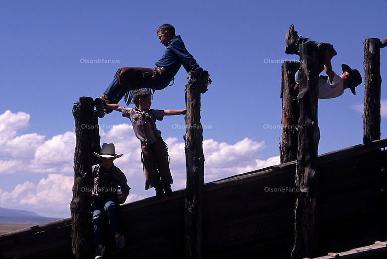 Children of the Davies family turn a ranch cattle chute into a homegrown playground on the Roaring Springs Ranch, near Steens Mountain in Oregon.  The young cow pokes learn to ride horses when they are young, and help move cattle on the ranch.